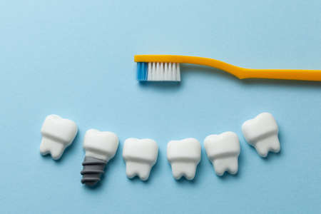 Healthy white teeth and implants on blue background with toothbrush. Stok Fotoğraf
