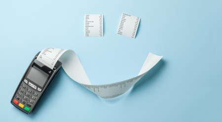 Terminal de caisse enregistreuse POS pour les paiements et ruban de papier à long rouleau en forme de sourire sur fond bleu