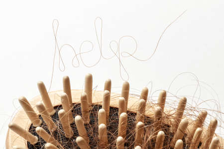 Hair loss. Comb with hair and inscriptions HELP. Concept of how to help and strengthen hair from falling out.