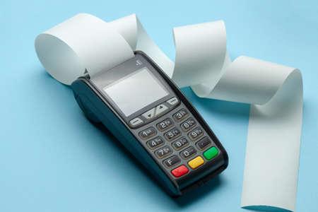 Terminal de la máquina de caja registradora POS para pagos y cinta de efectivo de rollo largo sobre fondo azul.