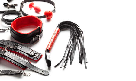 Set of toys for BDSM. The game of slavery with handcuffs, whip, gag and leather straps. Intimate games. Copy space for text