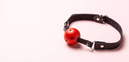 Red Ball gag on pink background. Intimate toys. Sex abuse slavery. Copy space for text