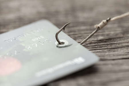 Credit card on fishing hook. Credit with trick or hidden payments. Online fraud.