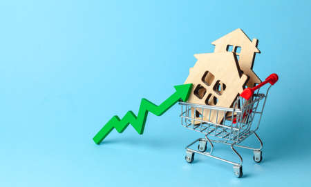 Up arrow and houses in shopping cart on blue background. Market growth in real estate prices. 写真素材 - 121964897