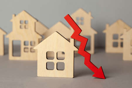 Pijl naar beneden en veel huizen. Dalende vastgoedprijzen markt. Huis kopen en verkopen. Stockfoto