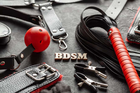 BDSM sex toys for adults. On black background whip, gag, handcuffs and leather straps. Stockfoto
