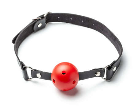 Red Ball gag in mouth isolated on white background. Intimate toys. Sex abuse slavery. Фото со стока