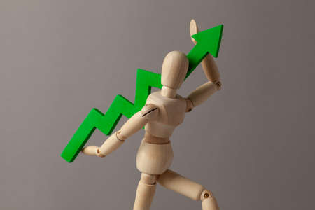 Businessman is holding a green up arrow. Deduction in the rise of indicators in the business at the expense of the leader 스톡 콘텐츠