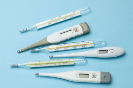 Termómetros médicos de vidrio y electrónicos sobre fondo azul.