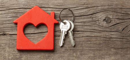 Drewniany czerwony dom i klucze na starych drewnianych deskach. Skopiuj miejsce na tekst