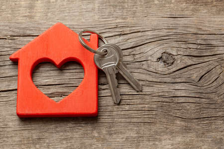Wooden red house and keys on the old wooden boards. Copy space for text 写真素材