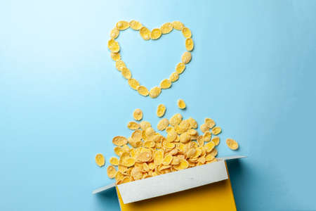 Scattered cornflakes out of box a heart shaped. Dry cereal breakfast. I love cereal Banque d'images