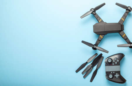 Drone with blades and remote control on blue background. Copy space for text