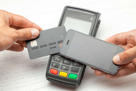 Contactless payment by credit card and smartphone phone. POS terminal NFC payment. Concept of how to choose payment method for shopping in a store 免版税图像