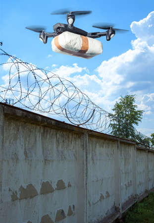 The drone flew across the sky with smuggling. The drone transports forbidden goods across the border breaking the law. Delivery of drugs through the wall with barbed wire. 스톡 콘텐츠