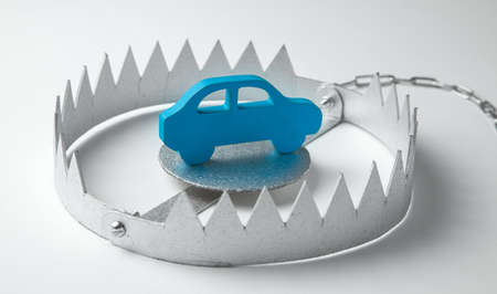 Trap with bait car. The risk of buying bad car. Car insurance. Gray background