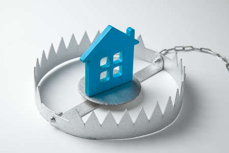 Trap with bait house. The risk of buying an old house. Dangerous mortgage. Home insurance. Gray background
