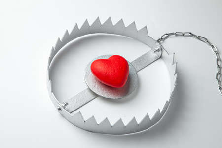 Trap with heart. Love is like bait. Gray background