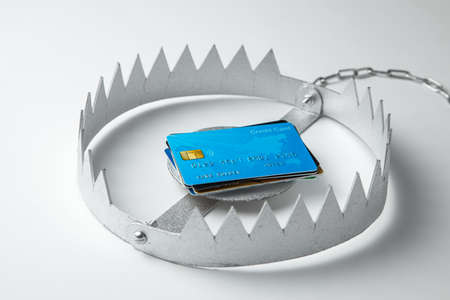 Trap with stack of credit cards. Unsafe credit risk. Gray background Stockfoto