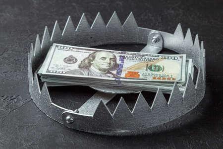 Trampa con una pila de dinero. Riesgo peligroso de inversión o engaño en los negocios. Fondo negro Foto de archivo