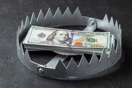 Trap with a stack of money. Dangerous risk for investment or deception in business. Black background Reklamní fotografie
