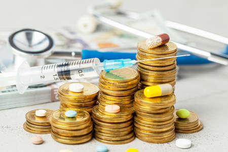 Stack of coins with pills and syringe on the background of stethoscope and cash money.