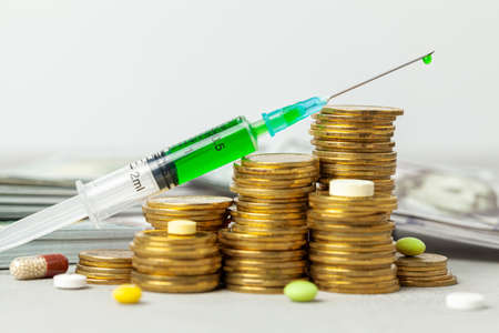 Stack of coins by staircase symbol of growth and pills with syringe with injection. Gray background with banknotes in the back.