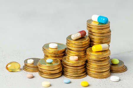 Stack of coins and colored pills on gray background. The concept of rising prices for medical services or insurance.