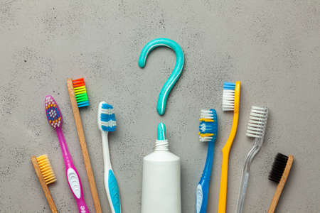 Toothpaste in the form of a question mark and many different and colored toothbrushes. Concept of how to choose the right toothbrush or how to brush your teeth