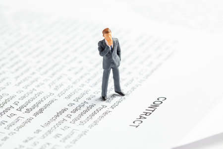 Businessman in a suit and tie ponders contact. Conclusion of an agreement between the companies and the employee. Zdjęcie Seryjne