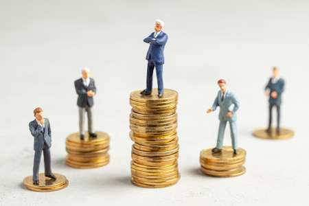 Successful businessman with big profits on stack of gold coins and less successful businessmen with small companies. Adequate investment in the company.
