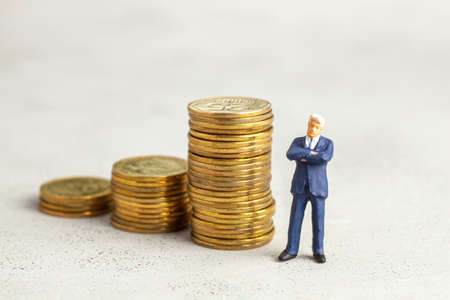 Successful businessman with big profits at the top of the stairs by coins. Adequate investment in the company