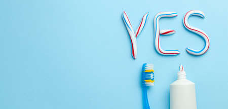 Word YES from toothpaste. Tube of colored toothpaste and toothbrush on blue background. The concept of proper cleaning and care of teeth. Copy space for text. Banque d'images - 129211578