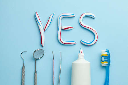 Word YES from toothpaste. A tube of colored toothpaste and a toothbrush and dentist tools mirror, hook on a blue background. The concept of proper cleaning and care of teeth. Banque d'images - 129212149