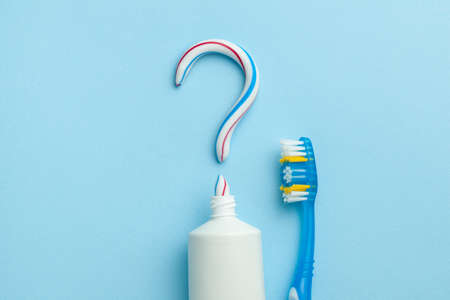 Question mark from toothpaste. The concept of choosing good toothpaste for teeth whitening. Tube of colored toothpaste and toothbrush on blue background Banque d'images - 129212173