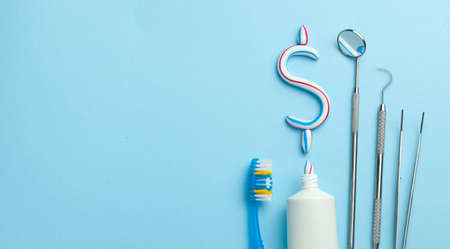 Dollar sign of toothpaste. Tube of colored toothpaste and a toothbrush and dentist tools, a mirror, a hook on a blue background. Concept expensive dentist services. Copy space for text. Banque d'images - 129212162