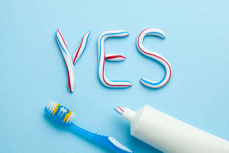 Word YES from toothpaste. Tube of colored toothpaste and toothbrush on blue background. The concept of proper cleaning and care of teeth. Banque d'images - 129212161