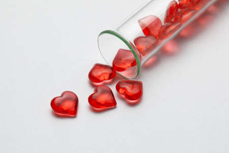 Hearts and test tube. Baby from tube vitro glass. Artificial insemination, IVF. Gray background.