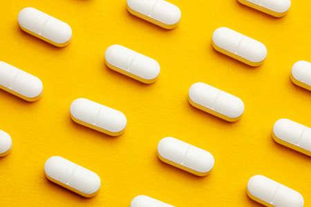 White pills on yellow background. Reklamní fotografie
