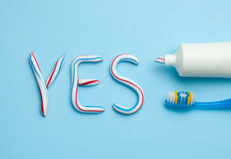 Word YES from toothpaste. Tube of colored toothpaste and toothbrush on blue background. The concept of proper cleaning and care of teeth. Banque d'images - 129213431