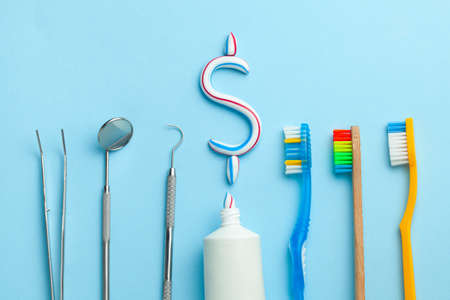 Dollar sign of toothpaste. Tube of colored toothpaste and a toothbrush and dentist tools, a mirror, a hook on a blue background. Concept expensive dentist services. Banque d'images - 129213439