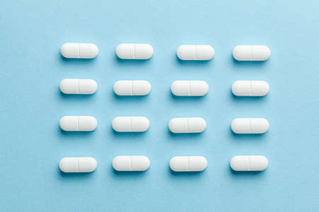 White pills on blue background. Reklamní fotografie