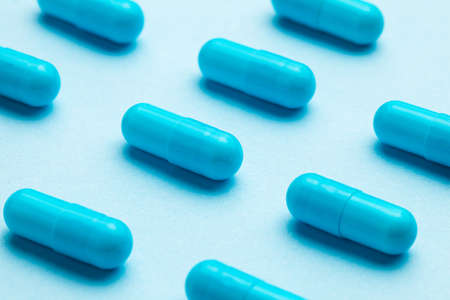 Blue tablets in capsules. Blue background