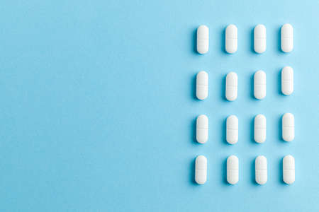 White pills on blue background. Copy space for text
