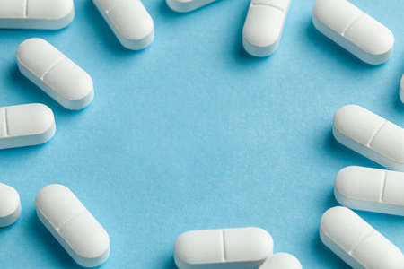 White pills on blue background. One tablet is broken in half, reducing the dose of the medicine. Frame. Copy space for text Reklamní fotografie