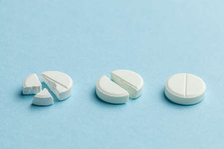 White pills on blue background. Few pills broken in half, reducing the dose of the medicine