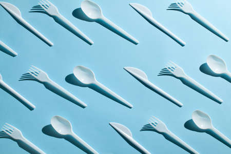 Plastic cutlery, forks, spoons and knives. Pollution of the environment with plastic and microplastics. Blue background Stok Fotoğraf