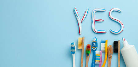Word YES from toothpaste. Tube of colored toothpaste and toothbrush on blue background. The concept of proper cleaning and care of teeth. Copy space for text Stock Photo
