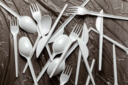 Plastic cutlery, forks, spoons and knives. Pollution of the environment with plastic and microplastics. Black plastic background.