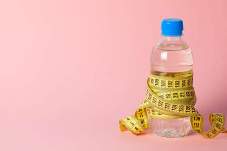 Plastic bottle with water and measuring tape on pink background. Copy space for text Stock Photo